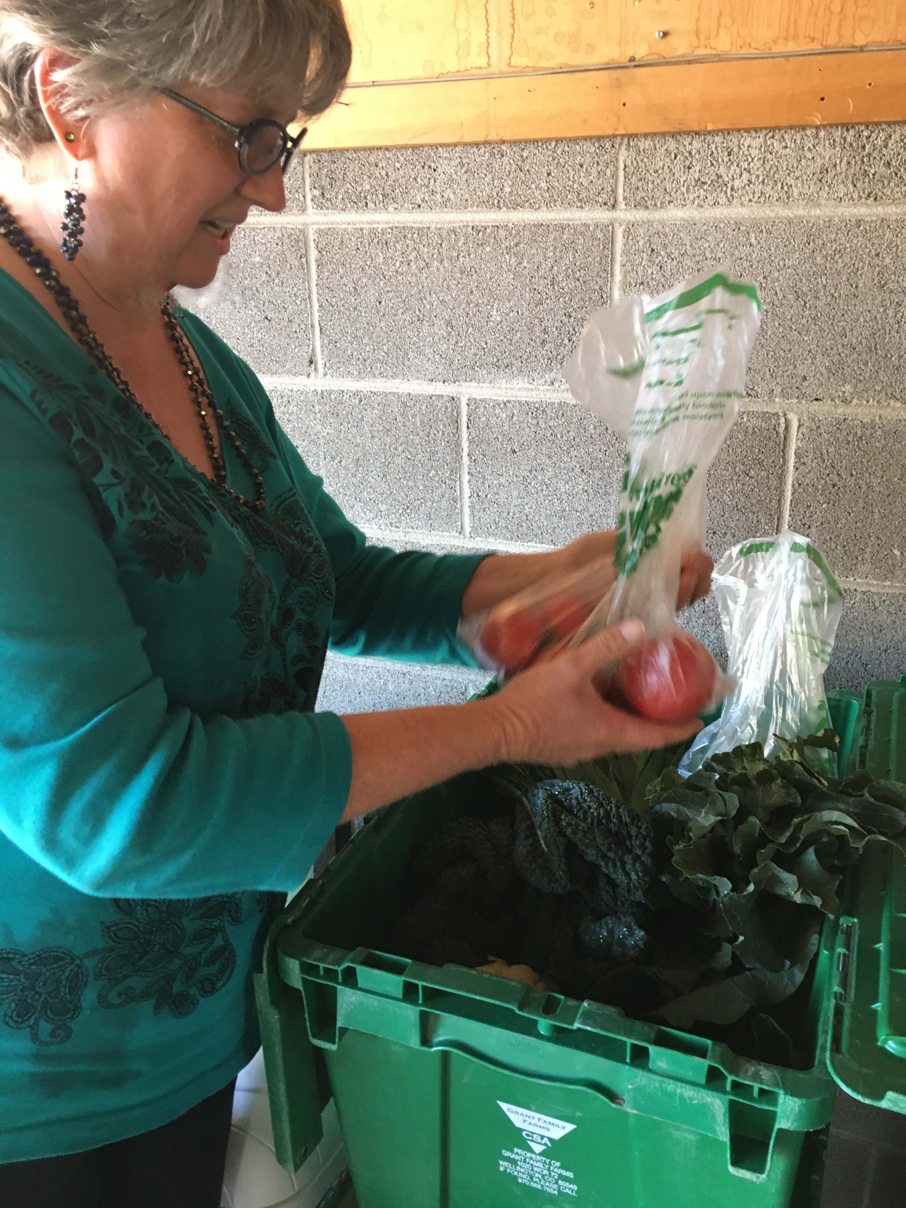 woman holding vegetables and unpacking them from bin