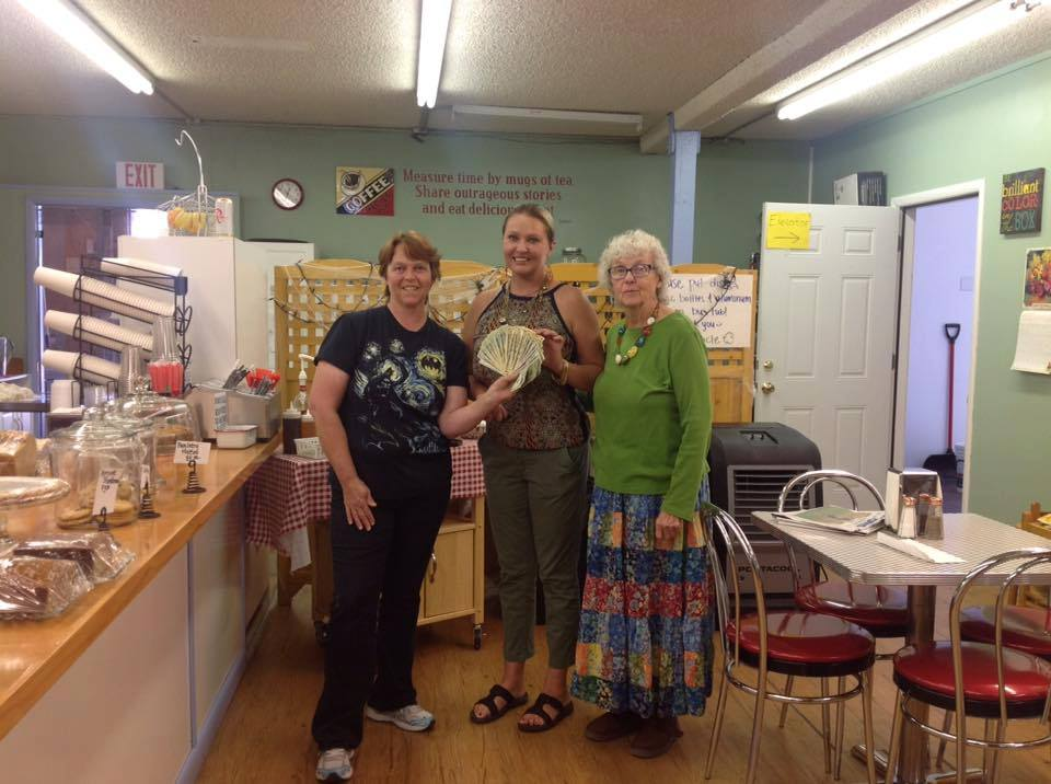 Local cafe owners holding money that they raised by crowdfunding
