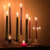 multiple lit candles in a dark room showing glowing light