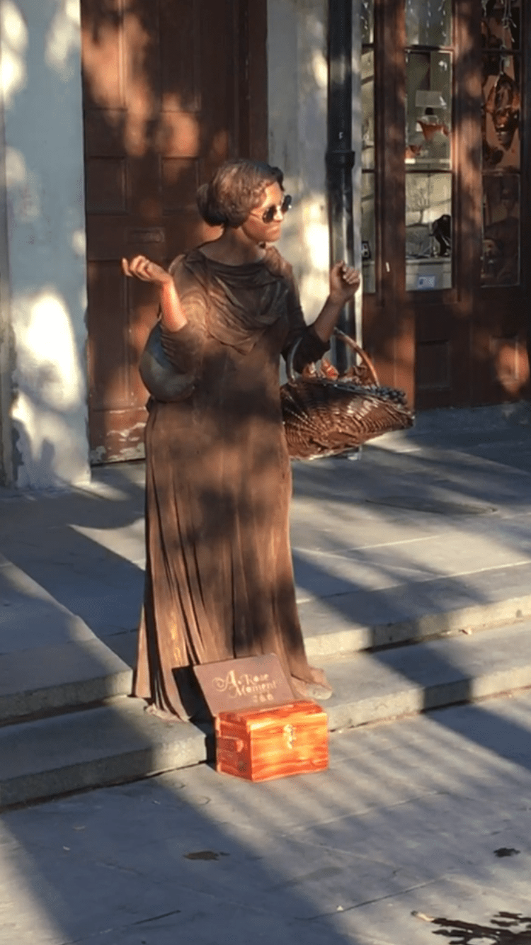 woman performing as a bronze statue in the street to collect money