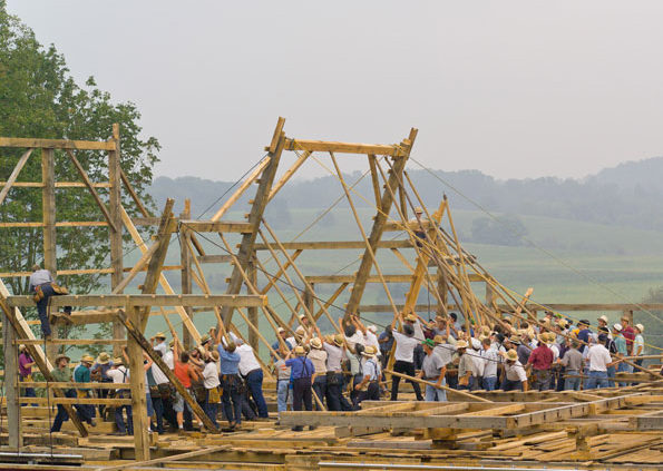 large group of men outside performing a barn raising in Walnut Creek, Ohio
