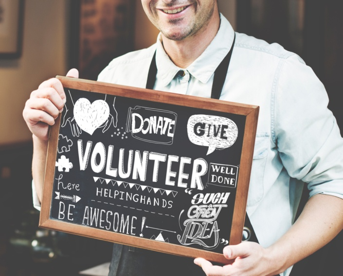 business owner holding sign that promotes giving donations volunteering