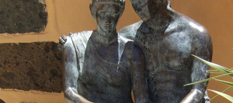statue of man and woman sitting together in comfort