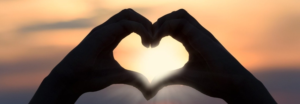 hands holding up a heart shape with sunrise