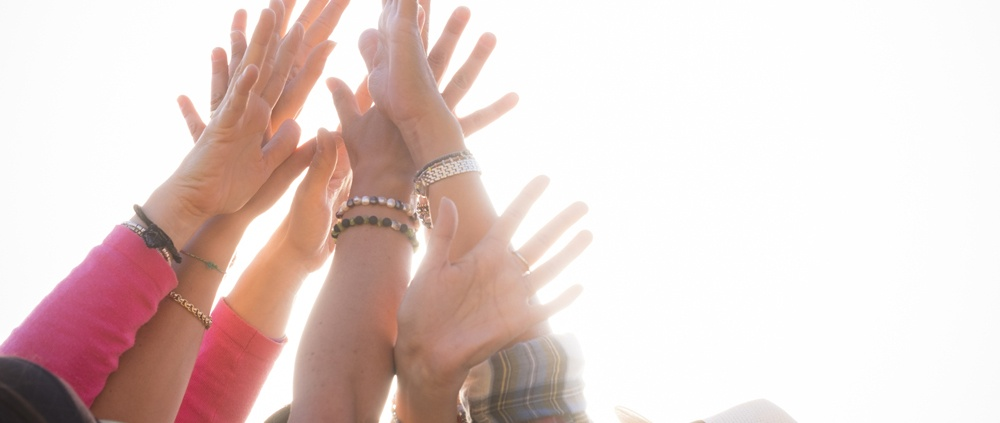 lots of hands held up in the air together as a group