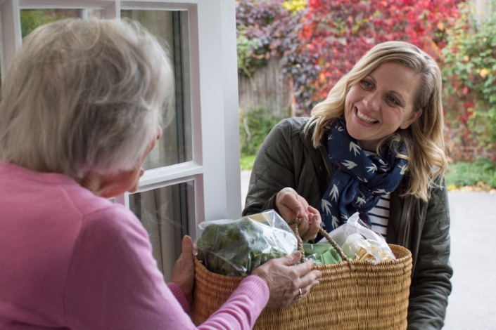 young woman providing groceries to elder neighbor