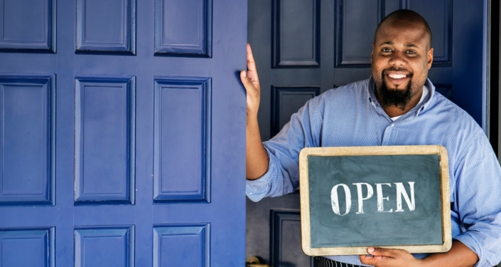 African American business man standing in front of shop with open sign