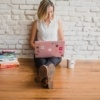 blond woman sitting on floor with laptop and marketing books