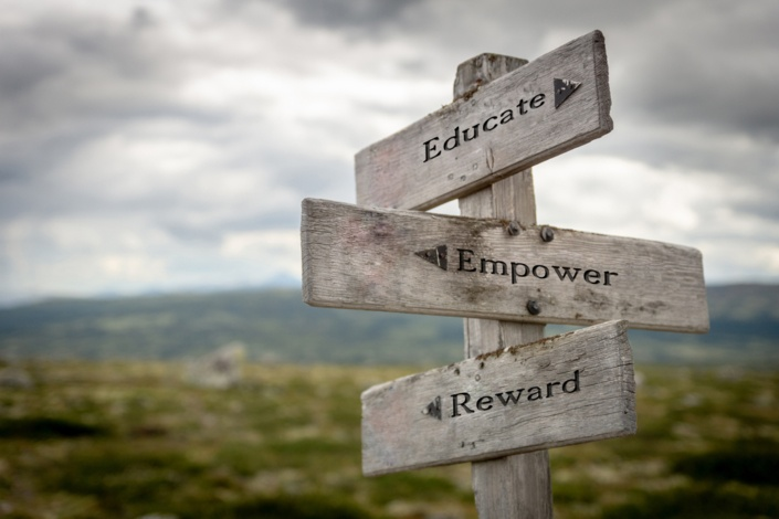 field with wooden sign stating educate, empower and reward