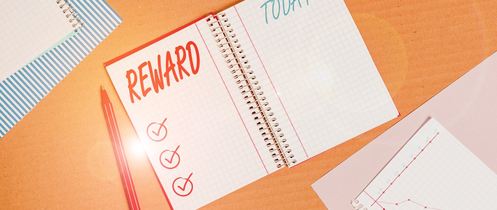 notebook with pen on table with rewards checkbox